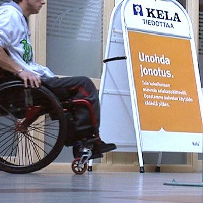 Mies pyörätuolissa Kelan toimistolla