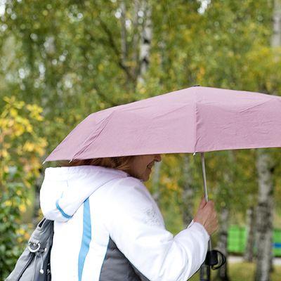 Nainen sateenvarjon alla.