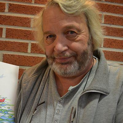 Heikki Eklöf piirtää kuvansa nopeasti. Kuvassa wenkoolit piirroshahmot ovat kalassa