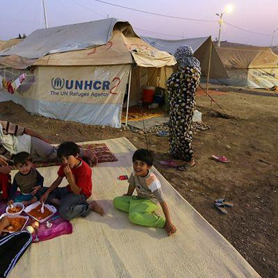 Pakolaisia syömässä ulkosalla viltin päällä