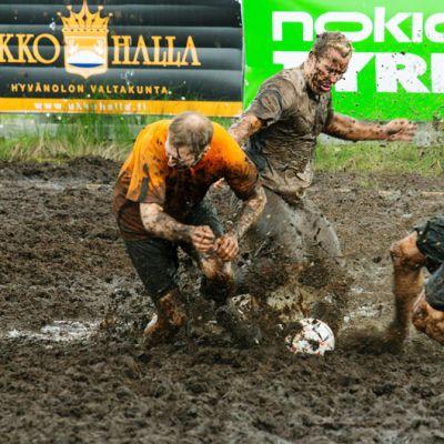 Telinekataja-joukkueen oranssipaitaiset pelaajat taistelevat pallosta FC Lerssin pelaajan kanssa.