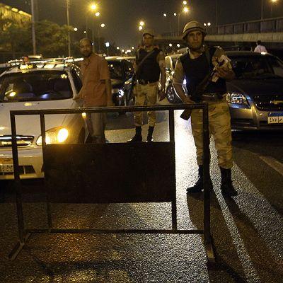 Egyptiläissotilaat tarkastavat autoja ulkonaliikkumiskiellona aikana tiesululla.