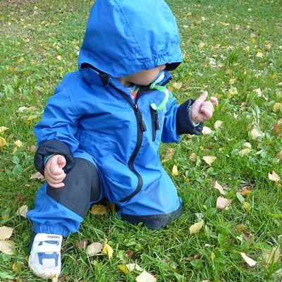 Siniseen haalariin pukeutunut pikkulapsi tutkii lehteä nurmikolla