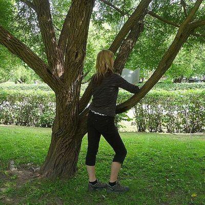Puuhun nojaava nainen lukee kirjaa selin kuvaajaan