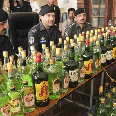 Pakistanin poliisi esittelee takavarikoimiaan alkoholipulloja.