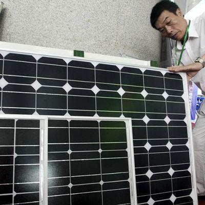 Kiinalainen mies tutkii aurinkopaneelia.