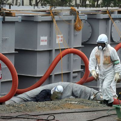 Puhdistustyöntekijä kävelee saastuneen veden säiliöiden vierellä Fukushiman ydinvoimalan alueella.