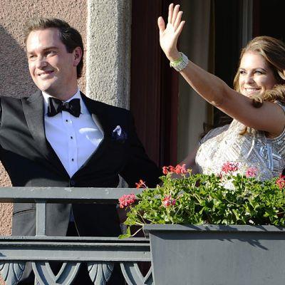 Prinsessa Madeleine ja hänen sulhasensa Chris O'Neill vilkuttavat Tukholman Grand Hotelin parvekkeelta.