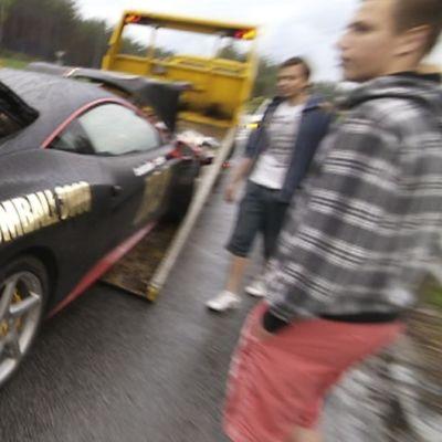 Kolaroitua Ferrari-urheiluautoa siirretään hinausauton kyytiin.