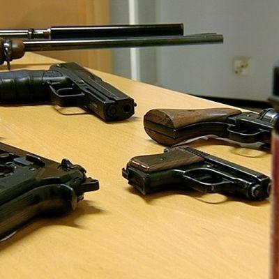 Poliisin takavarikoimia aseita pöydällä.