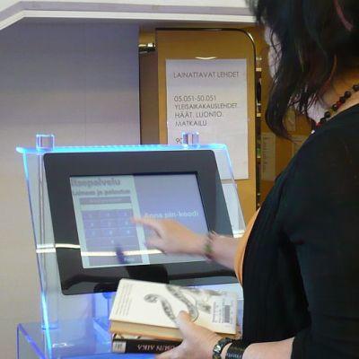 Kirjastotoimenjohtaja Inkeri Jurvanen kokeilee Hämeenlinnan pääkirjaston uutta itsepalveluautomaattia