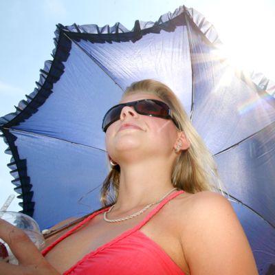 Nainen suojaa itseään auringonvarjolla.