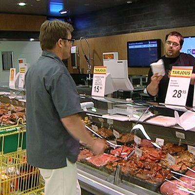 Myyjä ojentaa asiakkaan ostoksia lihatiskillä.