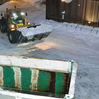 Kauhakuormaaja kerää lunta pihalta.