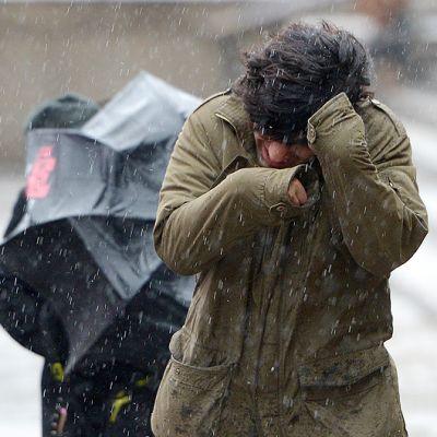 Ihmiset kävelevät jäätävässä sateessa ja kovassa tuulessa.