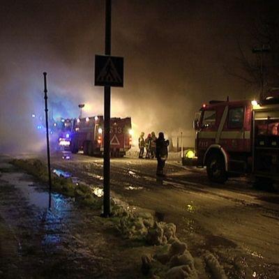 Paloautoja ja palomiehiä palopaikalla.