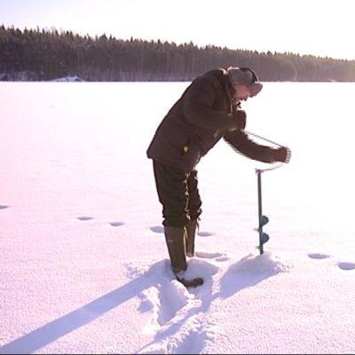 Mies poraa reikää jäähän.