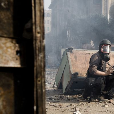 Valokuvaaja kaasunaamari päässä kaadetun myyntikojun takana kyyryssä.