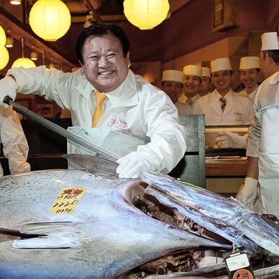 Mies leikkaamassa tonnikalaa suurella veitsellä.