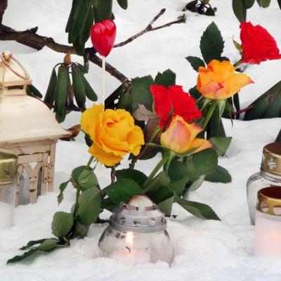 Kukkia ja kynttilöitä hautausmaalla.