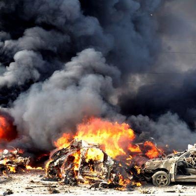 Pommi-iskussa tuhoutuneet autot palavat.