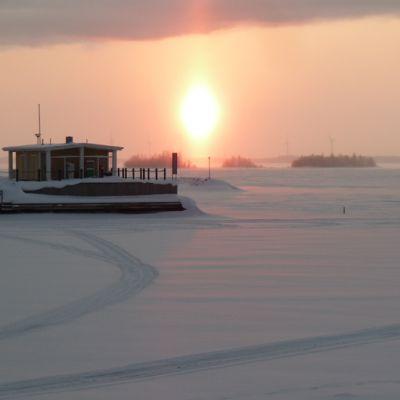 Aurinko laskee jäisen Perämeren taa.