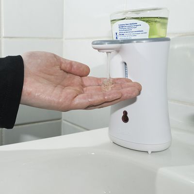 Henkilö käyttämässä saippua-automaattia.