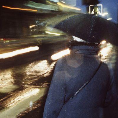 Nainen sateenvarjon kanssa kaupungin illassa.