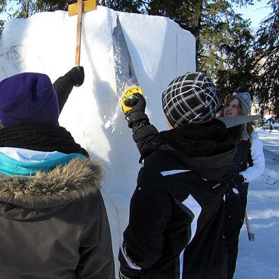 Koululaisia ja maahanmuuttajia tekemässä  yhteistä lumiveistosta