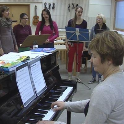Lehtori Anne-Mari Lindeberg opettamassa yhtyelaulua.