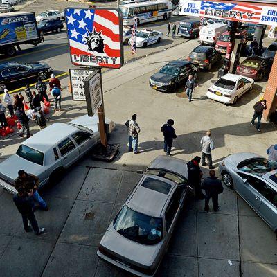 Ihmiset jonottavat bensakanistereiden kanssa bensiinitoimitusta brooklynilaisella huoltoasemalla.