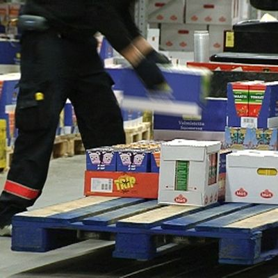 Henkilö lastaamassa ruokalaatikoita trukin kyytiin.