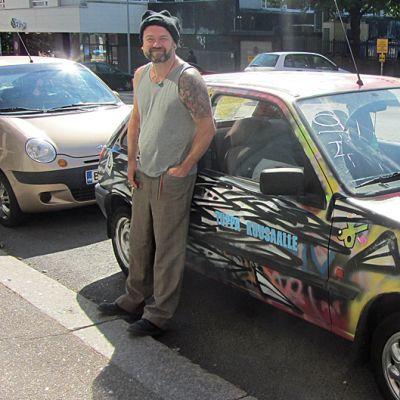 Taiteilija Jonne Pitkänen nojaa autoonsa.