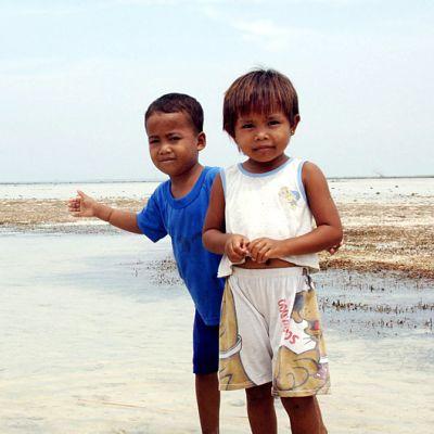 Kaksi lasta meren äärellä Indonesiassa.
