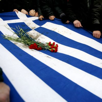Mielenosoittajat kantavat tuhriintunutta Kreikan lippua, jonka päällä on punaisia neilikoita.