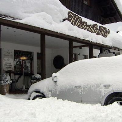 Lumeen peittynyt auto majatalon edessä
