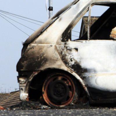 Palanut auto ja IRAn kyltti Lurganissa, Pohjois-Irlannissa, maaliskuussa 2009.