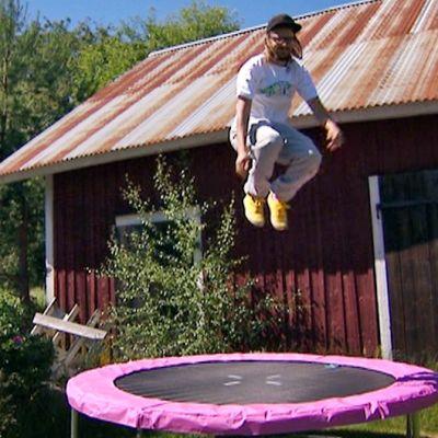 Jukka Poika pomppii vaaleanpunaisen trampoliinin päällä.