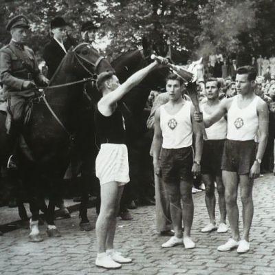 Olympiatuli on saapunut Hämeenlinnan torille 17.7.1952, tulen ottaa vastaan maileri Ossi Teileri, tulta ovat tuomassa Kisan urheilijat Åke Selin, Veikko Silvennoinen, Lauri Fagerlund ja Erkki Pulli.