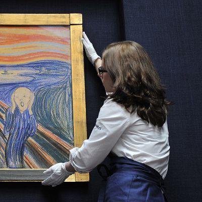 Sothebyn huutokauppakamarin työntekijä asettelee Edvard Munchin Huuto-maalausta esille.