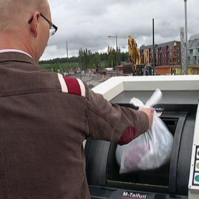 Mies laittaa roskapussin uuteen keräysastiaan