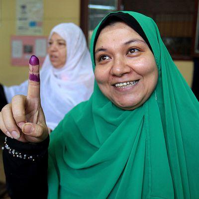 Egyptiläisnainen näyttää äänestyspaikalla Kairossa äänestämisen merkiksi musteeseen kastettua sormeaan, samaan aikaan kun toinen nainen pudottaa äänensä uurnaan.