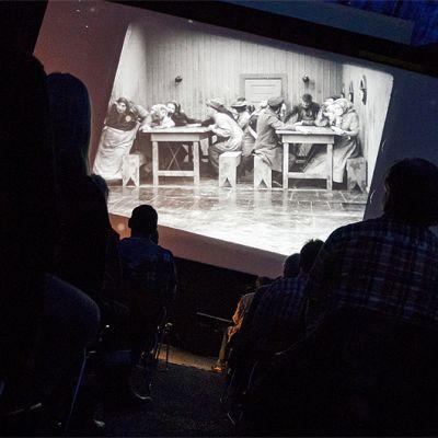 Ihmiset katselevat Charles Chaplinin Siirtolainen-elokuvaa Sodankylän filmifestivaaleilla.