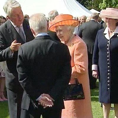 Kuningatar Elisabeth ja vieraita puutarhajuhlissa.