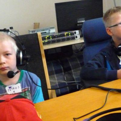 Kaksi pientä poikaa tekee radiolähetystä viestintäleirillä.