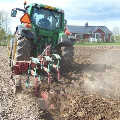 Maanviljelijä kyntämässä peltoa traktorilla.