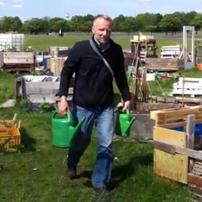 Mies kantaa kasteluvettä puutarhassa