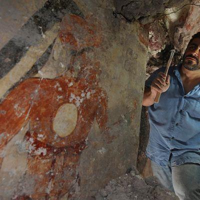 Arkeologi William Saturno puhdistamassa mayakaupunki Xultúnista löytyneen rakennuksen seinää.