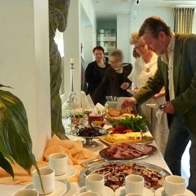 Ihmiset ottavat ruokaa seisovasta pöydästä