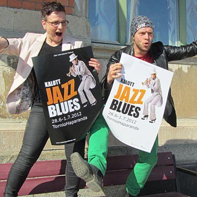 Kaksi henkilöä esittelee julisteita.